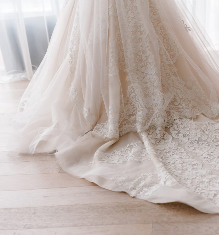The bottom of a luxurious white wedding dress with a long train. Morning bride in the house. Elegant wedding dress.