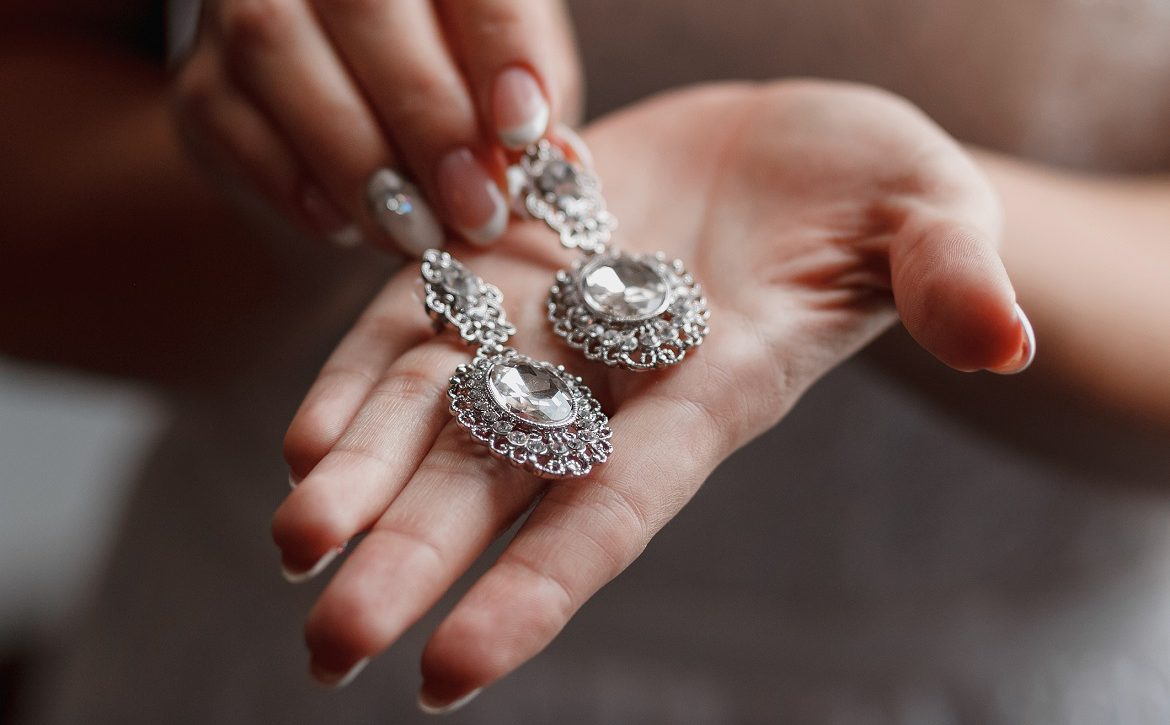 Wedding earrings on a bridal hand, bride's morning and jewelry accessories and decoration concept