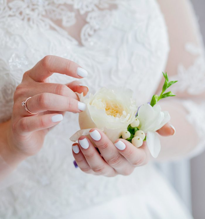 Close-up of the bride's hands holds a boutonniere. boutonniere with red rose